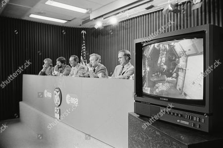 Media newspersons at left, left to right, Lynn Sherr, ABC; Gary Schweitzer, Cable News; Howard Benedict, The Associated Press; Roy Neal, NBC; and Morton Dean, CBS, asked question of the Spacelab scientist, in Houston, Texas. At right television picture of the floating scientists; Owen Garriott, Robert Parker, Byron Lichtenberg, and Ulf Merbold