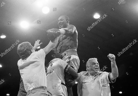 Mike McCallum is lifted up by his ring team after he retained his World Boxing Association junior middleweight title against Julian Jackson in Miami Beach, . McCallum pounded Jackson against the ropes in the second round, which proved to be the last as the referee stepped in the stopped the fight