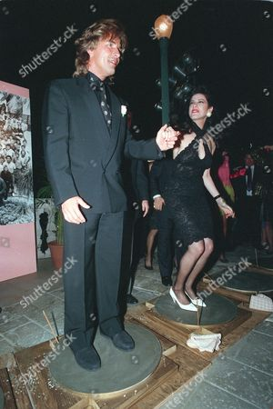 """Johnson Santiago Actor Don Johnson, left, and Saundra Santiago, co-stars of the TV show """"Miami Vice,"""" jump up and down in order to immortalize their footprints in cement to commemorate the show's 100th episode at a party in Miami, Fl., Tuesday night"""
