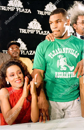 Actress Robin Givens applauds her husband, new world heavyweight champion Mike Tyson, after the knocked out Michael Spinks in he first round of their championship bout in Atlantic City, N.J., on