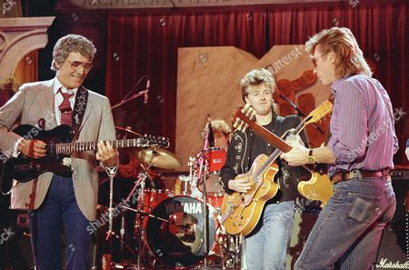 Rockabilly singer Carl Perkins, left, is shown rocking in the New Year on MTV with Brian Setzer of the Stray Cats and Dave Edmunds in New York