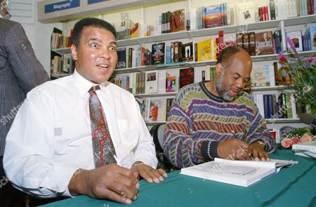 Muhammad Ali, left, smiles at fans while photographer Howard L. Bingham autographs a copy of his book on Ali at a bookstore in New York on . Ali and Bingham both signed copies of the book which is a photographic essay compiled from pictures that Bingham had taken of Ali over the last 30 years