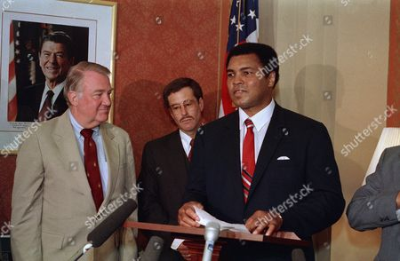 Attorney General Edwin Meese III looks on as former heavyweight champion Muhammad Ali, right, tells reporters that Michael Spinks will take the title from Mike Tyson in their upcoming fight on Tuesday on Capitol Hill in Washington. Ali met with newsmen on in Washington, in support of Stephen A. Saitzburg, center, who will be joining the Justice Department as the deputy assistant attorney general in the criminal division