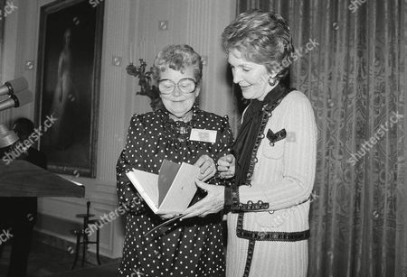 Stock Photo of First Lady Nancy Reagan receives a gift of a trustee handbook from Mrs. Esther Anderson, Chairman of the Trustee Committee of the American Association of Museums during a reception for the group at the White House on in Washington. Anderson is from Boston, Mass