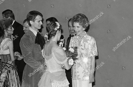 First Lady Nancy Reagan receives flowers from Denise Jackson, a member of the Joffrey Ballet in Los Angeles at night on after the troupe's opening night performance. Cast member Phillip Jerry waits to be received by the First Lady as Robert Joffrey looks on from behind Mrs. Reagan