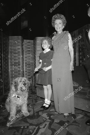 """First lady Nancy Reagan shown with 10 year old Aileen Quinn, who plays Annie in the new movie musical """"Annie,"""" at the premier of the movie in New York's Radio City Music Hall on . Annie's dog, Sandy, watches the festivities at the benefit showing"""