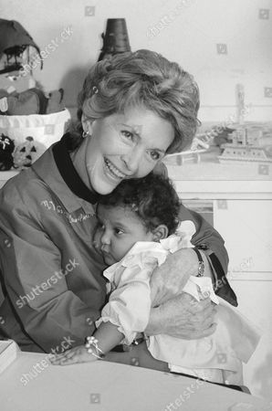 First Lady Nancy Reagan hugs Taina Gomez, 22-months-old, in the playroom of the Columbia-Presbyterian Medical Center in New York . Mrs. Reagan was in New York to review a federal foster grandparents program
