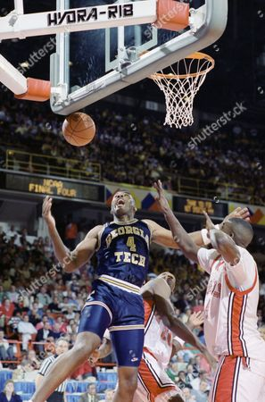 Georgia Tech's Dennis Scott reacts as he loses the ball during the first half of their NCAA Final Four Semi-final game with the UNLV Runnin' Rebels, in Denver. At right is UNLV's Larry Johnson