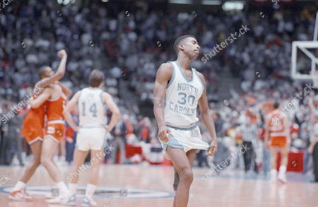 North Carolina's Kenny Smith, right, walks off the court leaving celebrating Syracuse Orangemen Derrick Coleman, left, and Rony Seikaly to their moment. North Carolina's Jeff stands at center. Syracuse beat North Carolina 79-75 in the NCAA East Regional Final, in East Rutherford