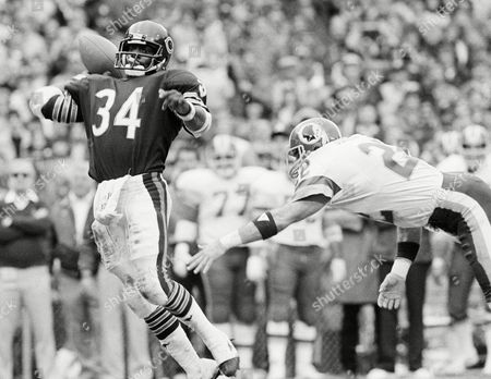 Stock Picture of Chicago Bears running back Walter Payton (34) eludes Washington Redskins safety Curtis Jordan (22) to throw a 19-yard touchdown pass to Pat Dunsmore in the second quarter of a NFC playoff game, at RFK Stadium in Washington. The Bears won 23-19