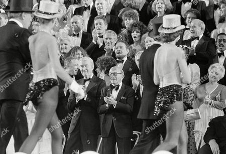 """Gene Kenth, Jimmy Stewart, Elizabeth Taylor, George Bundy, Diane Deaton, Allfred Drake, Ginger Rogers, Paul Newman, Ethel Merman, Martin Balsam, Farley Granger, Pam Dawber, Joan Collins, Richard Kiley, Arlene Dahl The stars applaud as Radio City Musical Hall Rockettes leave the stage after the """"Night of the 100 stars"""" at Radio City in New York, in a benefit for the Actors' Fund of America. From front are: Gene Kelley, Jimmy Stewart, Elizabeth Taylor, George Burns Diane Deaton, Alfred Drake, Ginger Rogers, Paul Newman, Ethel Merman, Martin Balsam, Farley Granger, Pam Dawber, Joan Collins and at the top Richard Kiley and Arlene Dahl"""