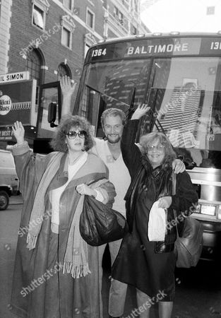 "Three members of the cast of the new Broadway production of Tennessee Williams' ""The Night of the Iguana,"" wave in front of the bus that will take them and the rest of the cast for a four-week pre-Broadway tryout before the show opens in New Yor, . Eileen Brennan, left, Roy Dotrice, center, and Jeanne Moreau, right, all stars in the show lead the fifteen-member cast to their Baltimore debut on Wednesday"