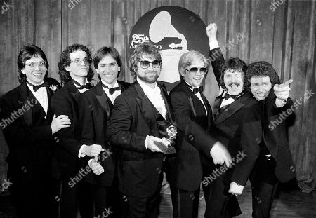 Toto Band members, from left, Jeff Porcaro, Steve Porcaro, Michael Porcaro, Dave Paich, Dave Herngate, Bobby Kimball and Steve Lukather, of Toto pose after winning six Grammys during the 25th Annual Grammy Awards presentation in Los Angeles. Mike Porcaro, who was the son and brother of prominent musicians and carved out a long, successful career as the bass player for the Grammy-winning pop group Toto, has died at age 59. Porcaro died, Toto's publicist Keith Hagen told The Associated Press