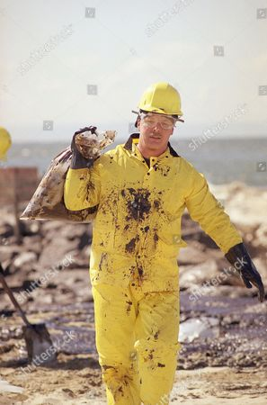 Stock Image of Tony Eaton With his protective garb splattered with oil cleanup worker Tony Eaton of Fontana, Calif., walks away from the oil-covered beaches of Newport Beach, California, with a plastic bag full of sand and oil. Bitter northwest winds and heavy seas heaved the gooey sludge ashore on Wednesday