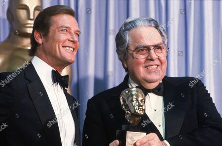 "Moore Broccoli Albert ""Cubby"" Broccoli, producer of the ""James Bond"" series, holds the Thalberg Award he received for his work at the Academy Awards in Los Angeles, Ca., . Roger Moore, left, British actor who plays secret agent 007 James Bond, made the presentation"