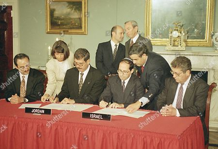 Fayez Tarawneh, Jordan's ambassador to the U.S., seated left, and Elyakim Rubinstein, head of the Israeli delegation to the Jordan-Israel peace talks, sign an agreementat the State Department, in Washington, D.C., setting a framework for resolving long-standing difference between them. U.S. Secretary of State Warren Christopher, standing right, talks to Victor Posuvaluk of the Russian Foreign Ministry during the signing. Others are unidentified aides