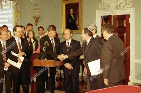 Fayez Tarawneh, Jordan's ambassador to the U.S., left, shakes hands with Elyakim Rubinstein, head of the Israeli delegation to the Jordan-Israel peace talks, after they signed a peace agreement at the State Department, in Washington, . Victor Posuvaluk of the Russian Foreign Ministry, centre, and US Secretary of State Warren Christopher, obscured behind Rubinstein, look on