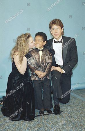 """Drew Lewis Actress Drew Barrymore gives """"Webster"""" star Emmanuel Lewis a congratulatory kiss following his being named """"Best Young Television Performer"""" at the 13th annual People's Choice Awards, in Santa Monica, Calif. Young man at right is unidentified"""