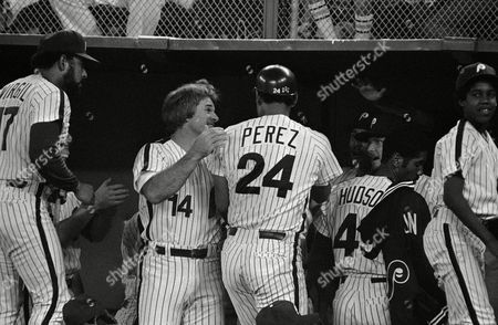 Philadelphia Phillies Pete Rose greets teammate Tony Perez in the dugout after Perez scored on a double by Garry Maddox in the fifth inning of play vs. the Pittsburgh Pirates at Veterans Stadium in Philadelphia