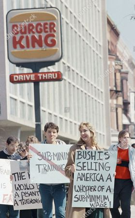 Two students carry signs on in Boston, outside a fast-food restaurant during a demonstration against a proposed training wage being supported by some businesses and the Bush administration. Jonathan Hacker, 20, left, and Jeff Nickel, 21, say that wages for student workers in the area are already too low and that the training wage would be unfair