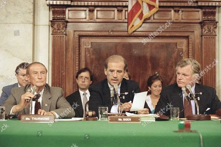 Stock Picture of Senate Judiciary Committee Chairman Joseph Biden, D-Del., center, reads from his tally sheet following the committee's voice vote to recommend Robert H. Bork for the Supreme Court, in Washington. Sen. Strom Thurmond, R-S.C., left, and Sen. Edward Kennedy, D-Mass., listen