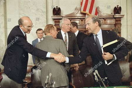 Senate Judiciary Chairman Joseph Biden, D-Del., right, shakes hands with Sen. Alan Simpson, R-Wyo., after the committee voted not to recommend the confirmation of Supreme Court nominee Robert Bork, during a meeting on Capital Hill in Washington, . Standing behind, from left center are Sens. Strom Thurmond, R-S.C., back to camera, and Patrick Leahy, D-Vt