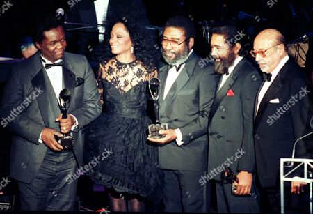 """Holland Dozier Ross Singer Diana Ross, second from left, joins songwriters, from left, Lamont Dozier, Brian Holland and Eddie Holland after the writing team was inducted into the Rock and Roll Hall of Fame in New York City, . Greatest hits written by the three collaborators include song sung by Ross and The Supremes, such as """"Baby Love,"""" """"I Hear a Symphony,"""" and """"Stop in the Name of Love."""" The man at far right is not identified"""