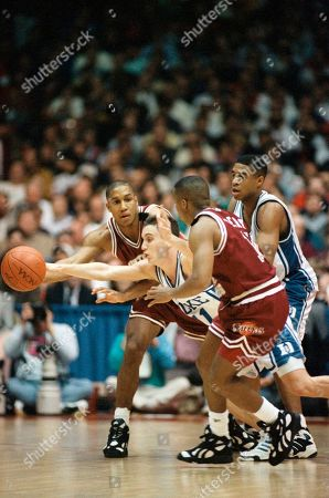 Stock Picture of Dukes Bobby Hurley, center, slips between Southern Illinois Tyrone Bell, rear, and Chris Lowery as Dukes Thomas Hill follows behind during their first-round NCAA tournament game at the Rosemont Horizon, Rosemont, Ill. Duke won the game 105-70