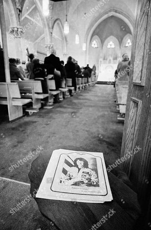 Parishioners stand in prayer during mass at St. John?s Church in Concord, New Hampshire, the hometown of Christa McAuliffe who was killed in the space shuttle explosion on Tuesday. A photo of McAuliffe adorns the cover of the church service program and is inscribed with her words, ?Beach for the stars