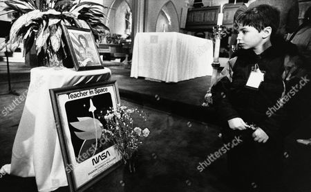 An unidentified boy looks at a shrine set up in memory of Christa McAuliffe at St. John's Church in Concord, New Hampshire, following a memorial service in her honor. McAuliffe was killed in the explosion of the Space Shuttle Challenger on Tuesday