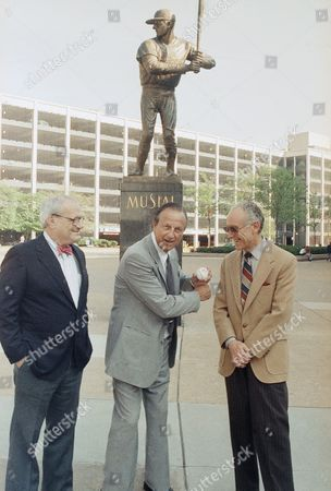 Co-founders of the ?Stan Musial Society?, Frank Mankiewicz, left, and Vic Gold, right, meet former member of the St. Louis baseball Cardinals and Hall of Famer Stan ?The Man? Musial in front of Busch Stadium in St. Louis, prior to the start of the Cardinals Giants baseball game. In the background is a larger than life statue of the baseball great, Stan Musial