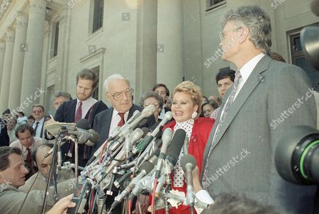 """Davis Bakker Tammy Faye Bakker, wife of fallen PTL leader Jim Bakker, sings """"On Christ The Solid Rock I Stand"""" in front of the Federal Courthouse in Charlotte, N.C. after her husband was found guilty of all 24 counts of fraud and conspiracty, . At left beside Mrs. Bakker is her attorney, George T. Davis. Others are unidentified"""
