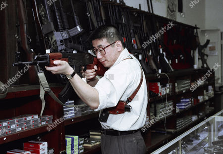 David Chu, manager of the Western Gun Shop shown here on in the Korea town section of Los Angeles checks a semiautomatic rifle at the store
