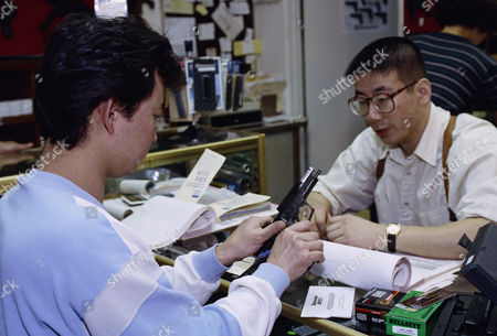 David Chu, right, manager of the Western Gun Shop in the Korean town section of Los Angeles, sells a 45-caliber handgun to Kang Chang at the store in Los Angeles. Chang said he was purchasing the gun because of concerns about unrest after the verdict in the second Rodney king beating trail