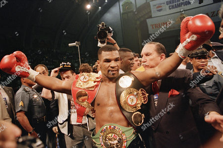 Undisputed heavyweight champ Mike Tyson shows off his three heavyweight title belts following his first round knockout of Michael Spinks in their world heavyweight title bout on in Atlantic City