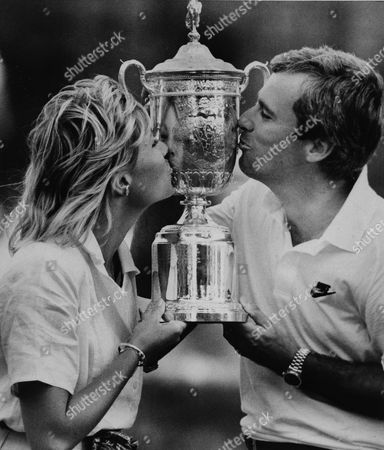 Curtis Strange, Sarah Strange Curtis Strange of Va., and his wife Sarah kiss the U.S. Open Championship trophy shortly after Strange defeated Nick Faldo of England in the 5th round playoff at the Country Club in Brookline, Mass