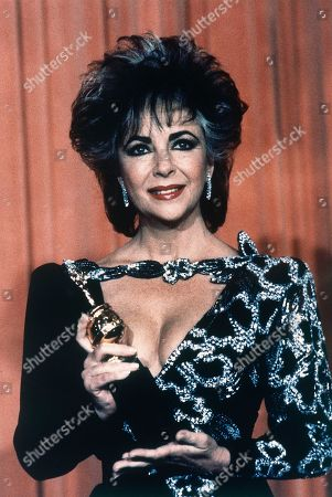 British-borne American actress Elizabeth Taylor poses with the prestige Cecil B. DeMille award after its presentation to her for her contribution to the entertainment industry in Beverly Hills, California, United States on