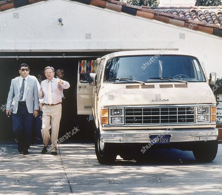 A van registered to the Pierce-Hamrock-Reed Mortuary of Los Angeles prepares to leave the home of the late film star Rock Hudson in Los Angeles, United Kingdom, on following the star's death. The two men on the left are security men at his home