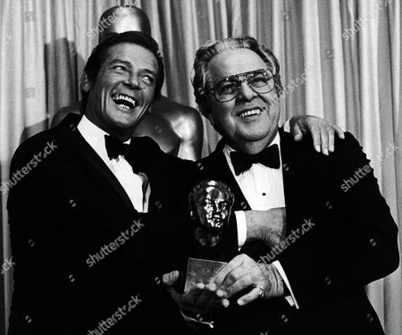 Actor Roger Moore, left, stands with Albert Broccoli, known as Cubby, after he presented Broccoli with the Irving Thalberg Award during the 54th Annual Academy Awards in Los Angeles, California, USA on