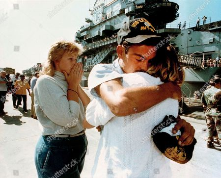 Stock Image of Michael Pando, Lisa Thomas, Samantha Sheppard Airman Apprentice Michael Pando is hugged by his girlfriend Lisa Thomas as friend Samantha Sheppard, left, sheds tears of relief after Pando arrived safe at port aboard the aircraft carrier USS Lexington, in Pensacola, Fla., . A Navy T-2 Buckeye jet crashed into the ship's island yesterday, killing it's training pilot and four others