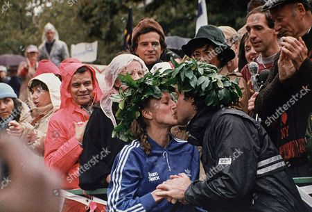 Grete Waitz (left) and male winner Rod Dixon, embrace in the winner's circle with their garland head wreaths after winning the New York City Marathon in New York. Waitz is from Norway and Dixon is from New Zealand