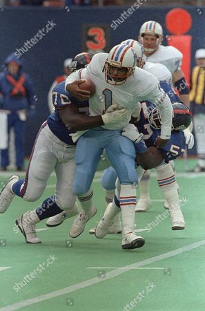 Warren Moon Houston Oilers quarterback Warren Moon is sacked for a five yard loss by New York Giants Leonard Marshall, left, and Corey Miller in the second quarter at Giants Stadium on in East Rutherford, New Jersey. The Giants won 24-20