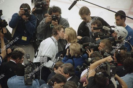 Stock Photo of Wayne Gretzky and Janet Gretzky share a kiss amid a throng of journalists on the Forum ice after Gretzky scored his NHL career record-setting 802nd goal, in Inglewood, Calif