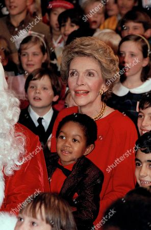 Nancy Reagan, Emmanuel Lewis With actor Emmanuel Lewis on her lap, first lady Nancy Reagan enjoys entertainment at a White House Christmas party, . Emmanuel and Santa helped over 350 diplomats' children celebrate the holiday