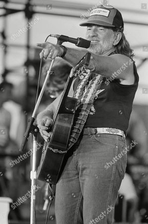 Singer Willie Nelson gestures to the crowd during his opening set at the FarmAid concert being held at the University of Illinois in Champaign on . Nelson spearheaded the drive to bring together over fifty acts to perform a benefit to aid America's Farmers