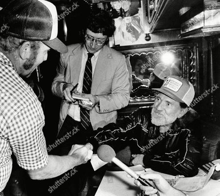 Country-western singer Willie Nelson, right, shakes hands with farmer Marvin Espenscheid who Nelson invited onto his bus to discuss farm problems at the Minnesota State Fair. Nelson was to have toured the cattle barn to talk with farmers, but the large crowd forced him to stay on the bus. Nelson announced that he will give a live-aid concert for farmers in Champaign,Ill. on Sept. 22.1985