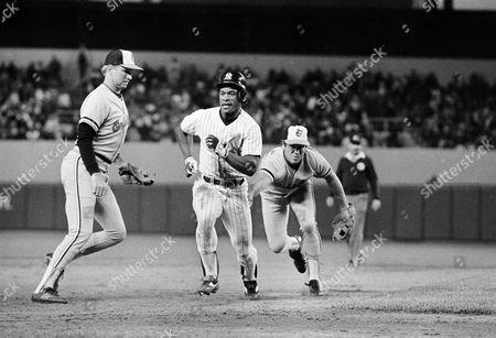 New York Yankees Rickey Henderson, center, is caught in a rundown between second and third base and put out on a tag by the Baltimore Orioles Cal Ripken, Jr. in the third inning of game, New York. It was the second steal attempt in the game for the AL leaders in stolen bases and he was picked off second by pitcher Scott McGregor