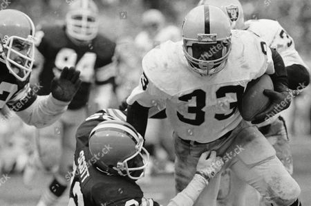 Oakland Raiders running back Kenny King breaks away from a tackle attempt by Cleveland Browns strong safety Clarence Scott for a gain in an AFC playoff game in Cleveland