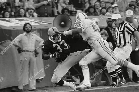 Oakland Raiders back Kenny King (33) falls on the Oilers three yard line holding on to a Jim Plunkett pass that set up Raiders touchdown in second quarter AFC wildcard playoff at Oakland on . Making the stop is Houston's Robert Brazile