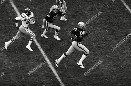 Stock Image of Oakland Raiders' Raymond Chester (88), right, runs towards the goal line for the first touchdown of the day against the San Diego Chargers on in San Diego, pursued by Chargers' Glen Edward (27). Chester caught the ball tipped by Raiders' Kenny King (33) in the first moment of the game and ran 65 yards for the touchdown. Raiders Bob Chandler (85) moves in for the block